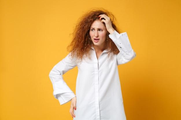 Zaabsorbowana młoda rudowłosa kobieta dziewczyna w białej koszuli pozuje na białym tle na żółtopomarańczowej ścianie