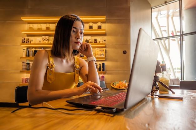 Zaakcentowana kobieta używa laptop w kawiarni