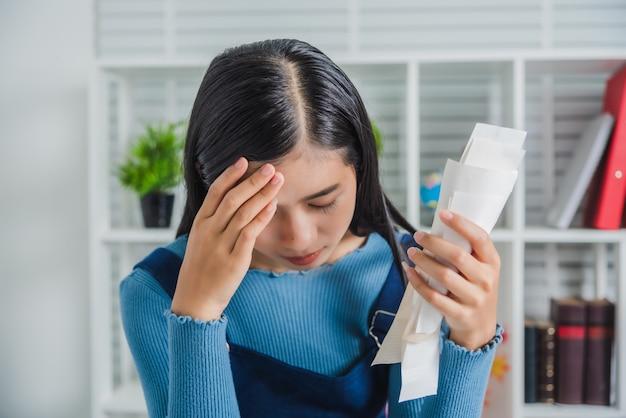 Zaakcentowana młoda azjatykcia kobieta administracyjna praca trzyma rachunki po robić zakupy online w specjalnym niższej ceny dniu i rabata kuponie