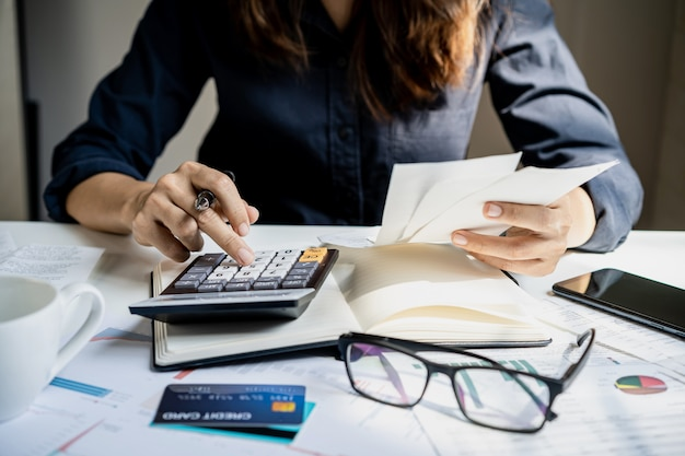 Zaakcentowana młoda kobieta sprawdza rachunki, podatki, saldo konta bankowego i oblicza wydatki w salonie w domu