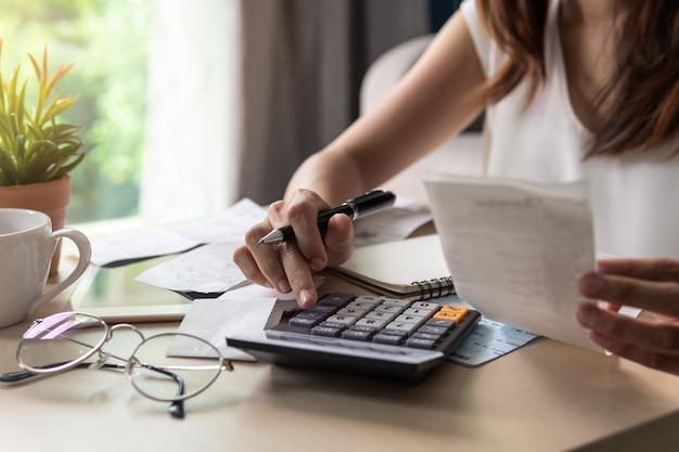 Zaakcentowana młoda kobieta sprawdza rachunki