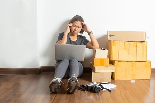 Zaakcentowane kobiety siedzi przy pracującym laptopem od pokoju domu