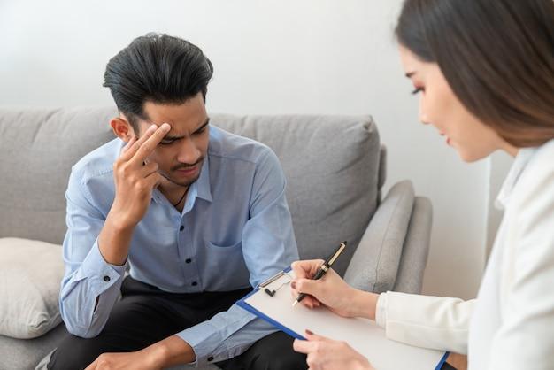 Zaakcentowany azjatycki młody człowiek cierpi na problem życia, siedząc na kanapie, podczas gdy kobieta psychiatra pisze informacje o swojej chorobie