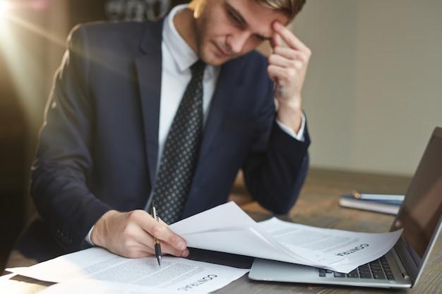 Zaakcentowany biznesmen pracuje z dokumentami kontraktowymi