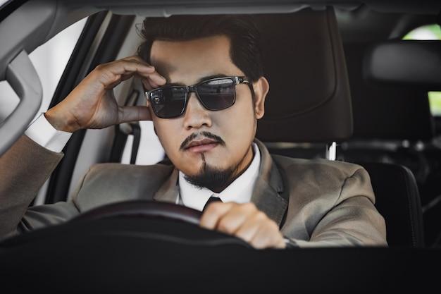 Zaakcentowany biznesowy mężczyzna jedzie samochód