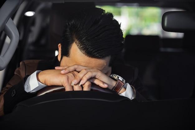 Zaakcentowany biznesowy mężczyzna jest zmęczony i śpiący w samochodzie