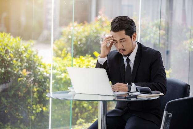 Zaakcentowany biznesowy mężczyzna używa laptop i pracującego problem