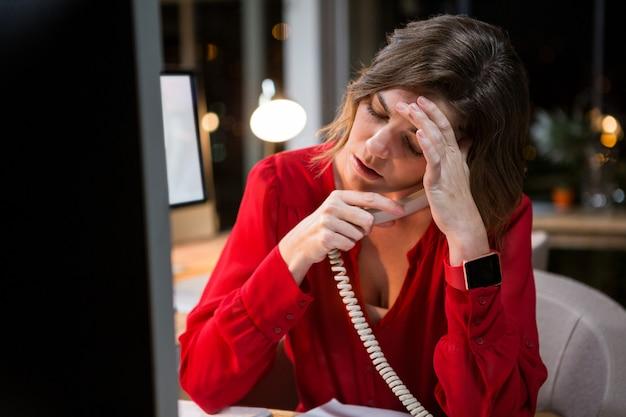 Zaakcentowany bizneswoman opowiada na telefonie przy jej biurkiem
