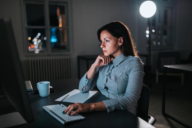Zaakcentowany bizneswoman pracuje nadgodziny. zbliżenie.