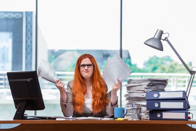Zaakcentowany bizneswoman z stertą papiery
