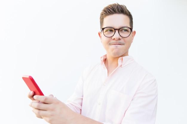 Zaakcentowany facet trzyma smartphone w eyeglasses