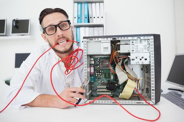 Zaakcentowany komputerowy inżynier pracuje na łamanych kablach