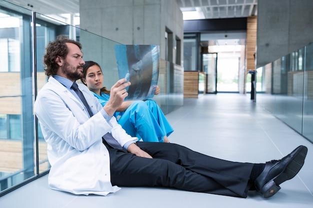 Zaakcentowany lekarz i pielęgniarka siedzi na podłodze, badając raport rentgenowski