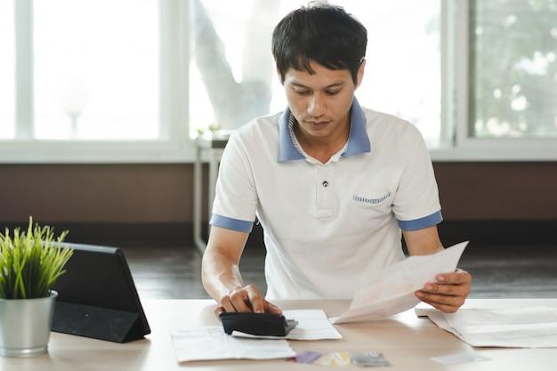 Zaakcentowany mężczyzna kalkulatorski kredytowej karty dług.
