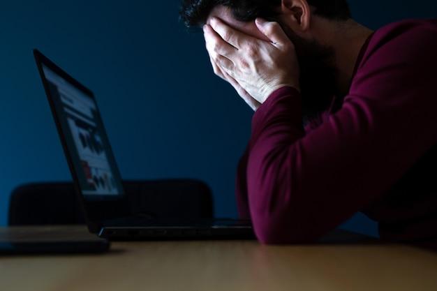 Zaakcentowany młody człowiek pracuje póżno na laptopie