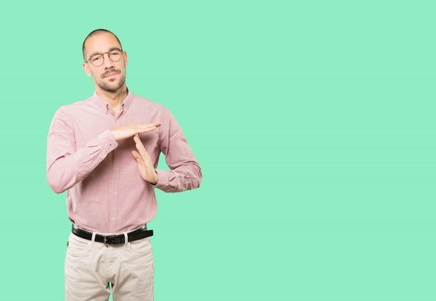 Zaakcentowany młody człowiek robi time-out gestowi rękami