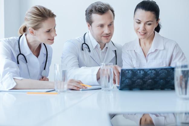 Zaangażował doświadczonego przystojnego neurochirurga pracującego i cieszącego się dyskusją z kolegami podczas analizy mrt