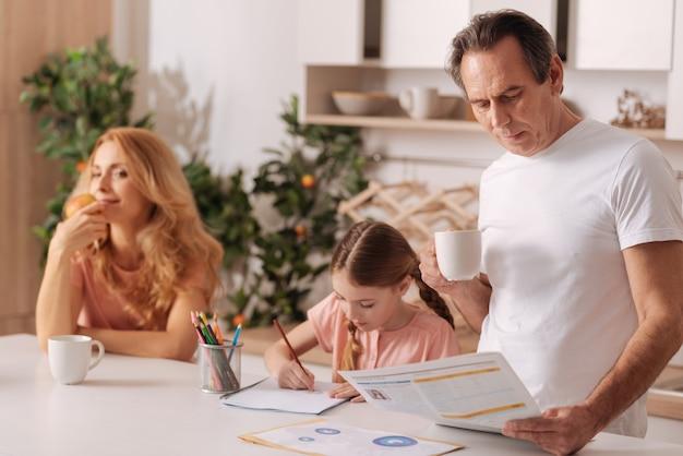 Zaangażowana pozytywna harmonijna rodzina siedząca w domu i relaksująca się, ciesząc się poranną rutyną