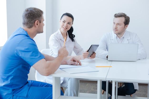 Zaangażowani przyjaźni wykwalifikowani praktycy pracujący w szpitalu i cieszący się rozmową, dzieląc się opiniami i korzystając z nowoczesnych gadżetów
