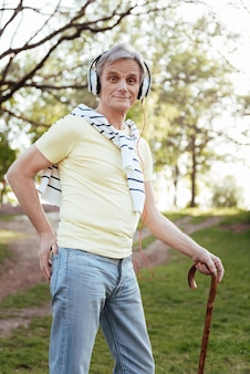 Zaangażowany czarujący staruszek korzystający ze słuchawek i opierający się na patyku podczas spaceru po parku i słuchania muzyki