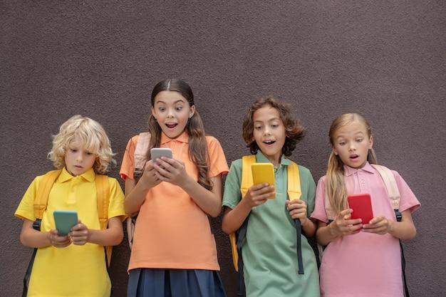 Zaangażowany. czwórka dzieciaków grających w gry online na swoich smartfonach i wyglądających na zaangażowanych