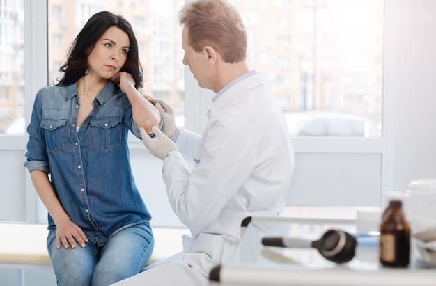 Zaangażowany doświadczony biegły dermatolog pracujący w klinice i umówiony na wizytę u pacjenta podczas badania skóry pacjenta
