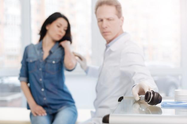 Zaangażowany poważny wykwalifikowany dermatolog pracujący w szpitalu i umówiony na wizytę u pacjenta podczas wykonywania dermatoskopu do badania skóry