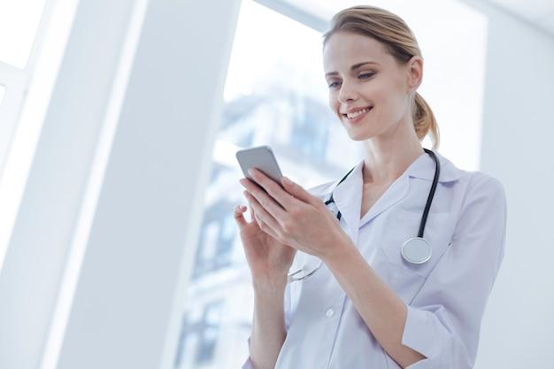 Zaangażowany radosny profesjonalny terapeuta pracujący w klinice, wyrażający zainteresowanie i wykorzystujący elektroniczny gadżet
