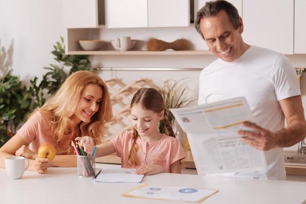 Zaangażowany uśmiechnięty przystojny mężczyzna czytający gazetę w domu i relaksujący się podczas porannej rutyny z żoną i córeczką