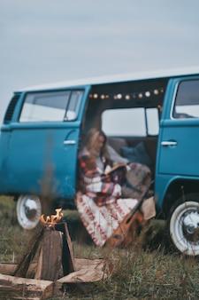 Zaangażowany w czytanie. atrakcyjna młoda kobieta okryta kocem, czytająca książkę, siedząc w niebieskim mini vanie w stylu retro retro
