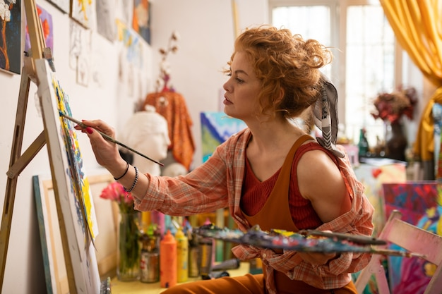 Zaangażowany w malowanie. rudowłosy artysta w stylowej koszuli czuje się zaangażowany w malowanie na płótnie