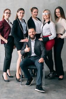 Zaawansowane szkolenie korporacyjne. pomyślny trener biznesu siedzi na krześle z kciukiem do góry. uśmiechnięty zespół profesjonalistów firmy stojących za.