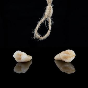 Ząb przedtrzonowy i kły po usunięciu z korzeniami nitką na czarnym tle