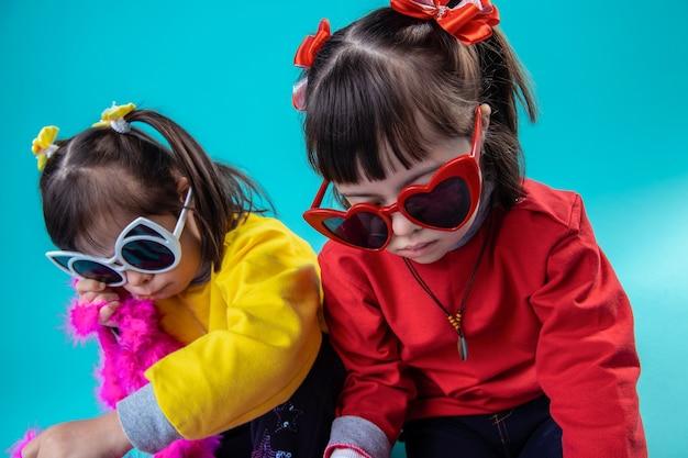 Zabawa dekoracją. ciemnowłosa dziewczyna z ogonami siedzi na gołej podłodze i nosi kolorowe okulary