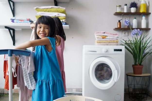 Zabawa dla dzieci szczęśliwa mała dziewczynka do prania ubrań i śmieje się w pralni