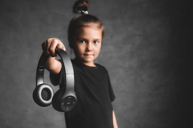 Zabawa emocjonalna skrzywiona dziewczynka z bezprzewodowymi słuchawkami i śpiewem, trzymając słuchawkę na szaro