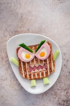 Zabawa halloweenowa kanapka z potworem z kawałkiem kiełbasy mięsa, jaj i sera na talerzu