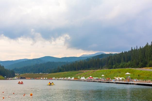 Zabawa klubu voda nad stawem wśród karpat. wynajem łodzi na wycieczkę po jeziorze.