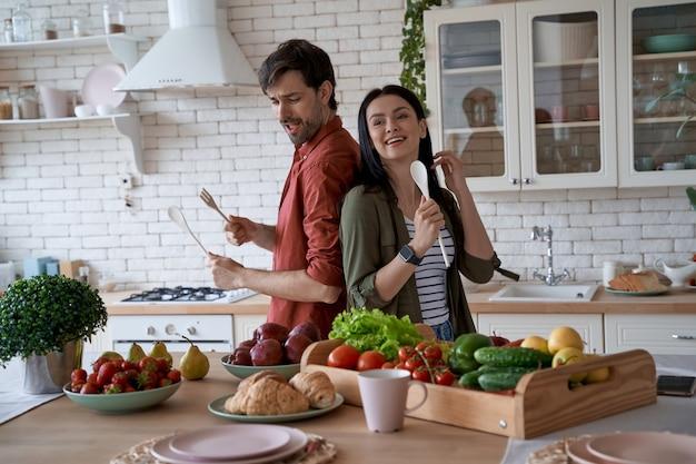 Zabawa młoda wesoła para rodzinna tańcząca i śpiewająca podczas przygotowywania zdrowego śniadania w
