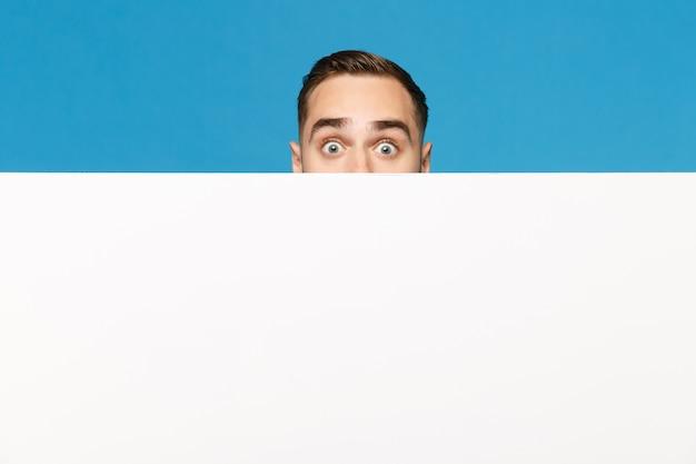 Zabawa młody człowiek ukrywa, wypatruj oczy duży biały pusty pusty billboard dla treści promocyjnych na białym tle na tle niebieskiej ściany portret studio. koncepcja życia emocje ludzi. makieta miejsca na kopię.