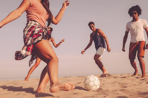 Zabawa na plaży. grupa wesołych młodych ludzi bawiących się piłką nożną na plaży