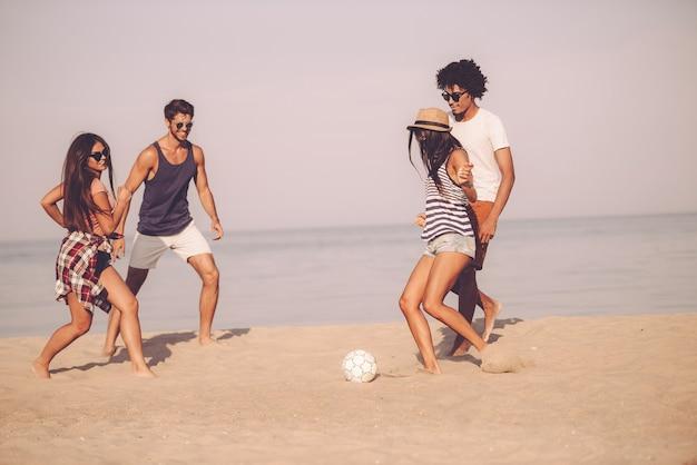 Zabawa na plaży z przyjaciółmi. grupa wesołych młodych ludzi bawiących się piłką nożną na plaży z morzem w tle