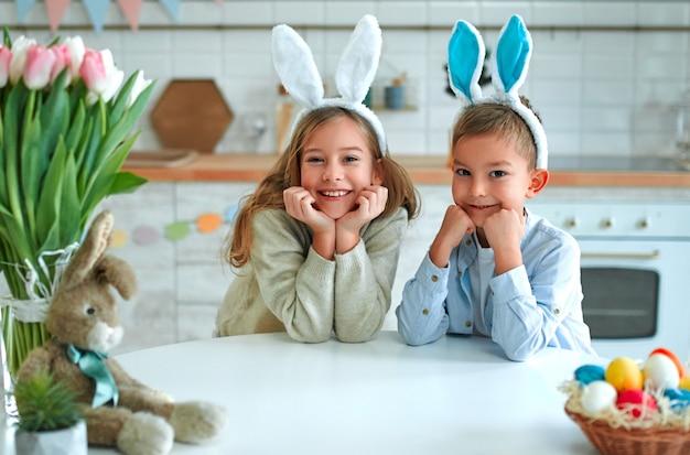 Zabawa na polowaniu na pisanki. chłopiec i dziewczynka dziecko nosi uszy królika i siedzi przy stole z rękami pod brodą. urocze dzieci świętują wielkanoc w domu.
