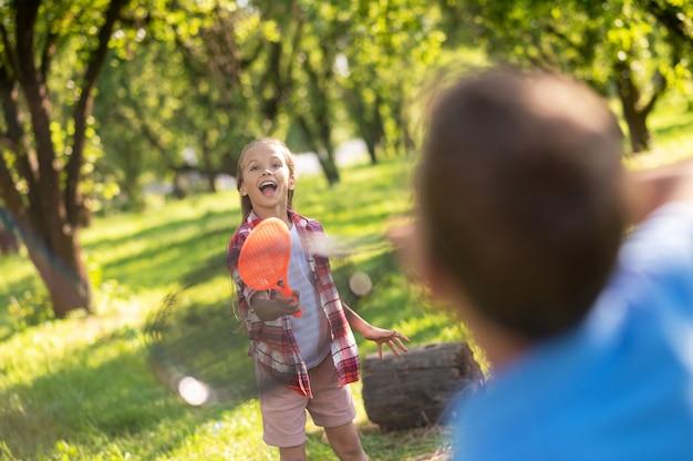 Zabawa na świeżym powietrzu. radosna dziewczyna z długimi blond włosami z rakietą tenisową i chłopcem tyłem do aparatu w parku w letni dzień