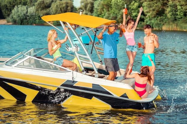 Zabawa na wodzie. grupa zabawnych wielorasowych przyjaciół bawiących się na nowoczesnej łodzi rekreacyjnej na rzece