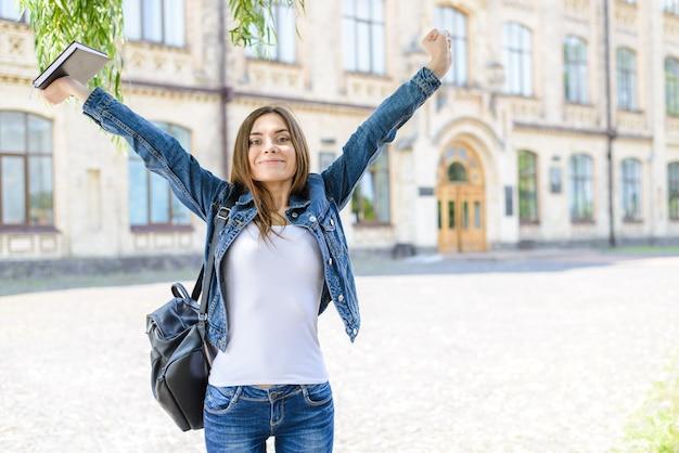 Zabawa radość wyrażenie emocji rozpocząć biznes koncepcja wolności wolnej. zdjęcie portret wesołej podekscytowanej ładnej ładnej dziewczyny podnoszącej ręce pięściami w górę patrząc na kamerę zamazaną na białym tle powierzchnię