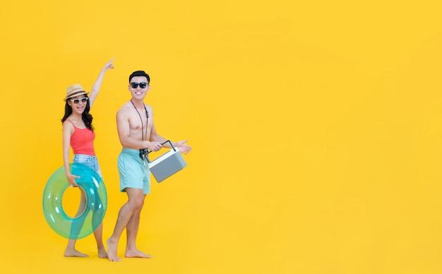 Zabawa szczęśliwa azjatycka para w strojach letnich na plaży z akcesoriami