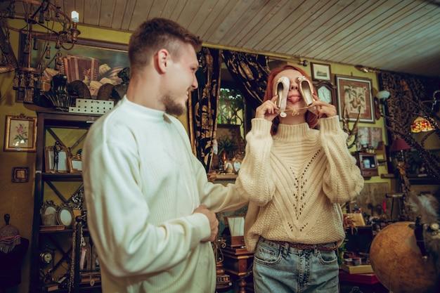 Zabawa. uśmiechnięta rodzina, kaukaski para szuka dekoracji domu i prezentów świątecznych w sklepie gospodarstwa domowego. stylowe i retro rzeczy na pozdrowienia lub projekt. renowacja wnętrz, świętowanie czasu.