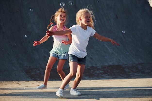 Zabawa z bąbelkami. zajęcia rekreacyjne. dwie małe dziewczynki bawią się w parku.