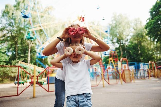 Zabawa z pączkami. wesoła dziewczynka jej mama dobrze się bawi w parku w pobliżu atrakcji.